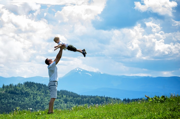 Glücklicher vater wirft einen kleinen sohn gegen einen grünen wald, berge und himmel mit wolken. vaterschaftsfreundschaft