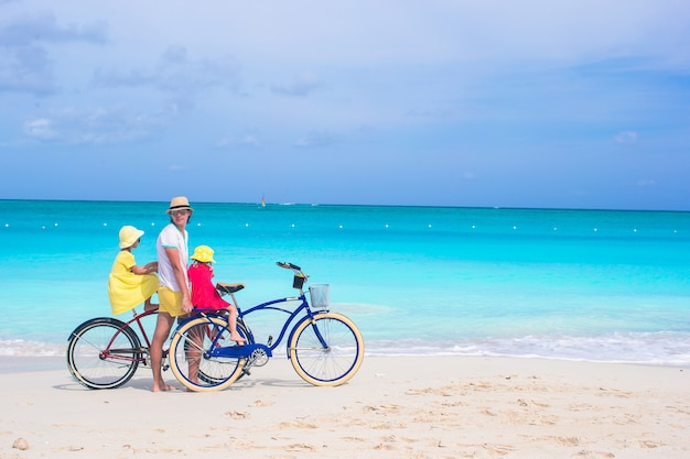 Glücklicher vati und nette mädchen, die fahrrad auf tropischen strand fahren