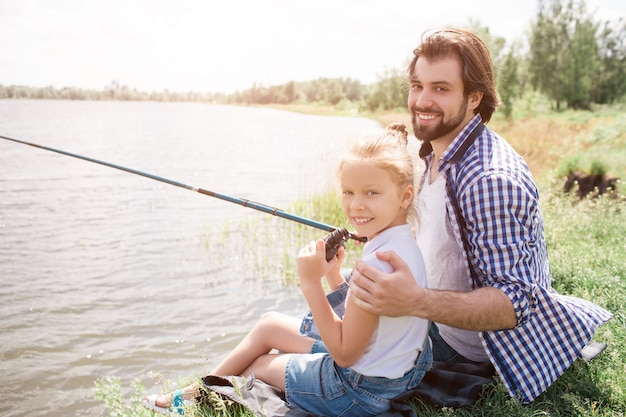 Glücklicher vati und tochter sitzen auf gras nahe wasser und betrachten kamera. er umarmt sie und hält die angelrute in der rechten hand. sie fischen.