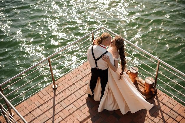 Glücklicher verheirateter mann und frau, die auf dem pier am see stehen. vorstellung der hochzeit