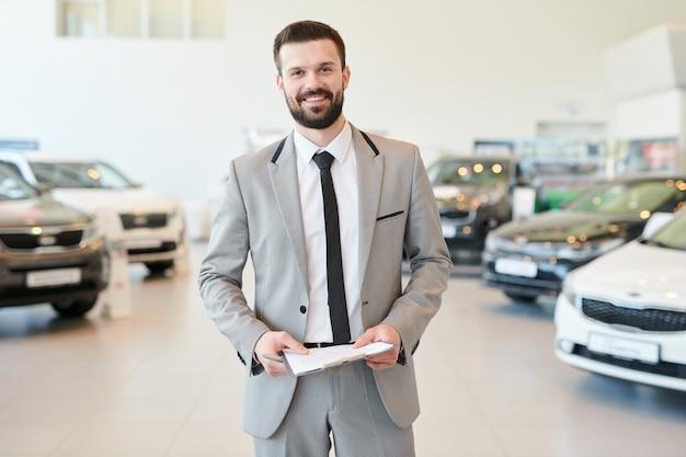 Glücklicher verkäufer mit vertrag, der am autosalon steht