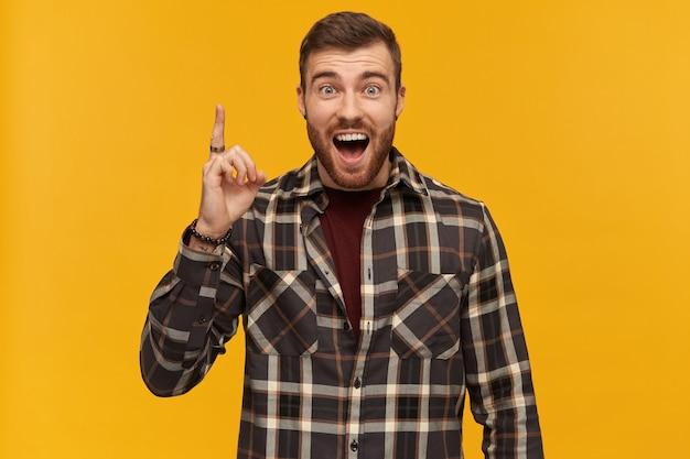 Glücklicher verlassener junger bärtiger mann im karierten hemd, der mit dem finger nach oben zeigt und eine idee hat, die über gelber wand isoliert wird