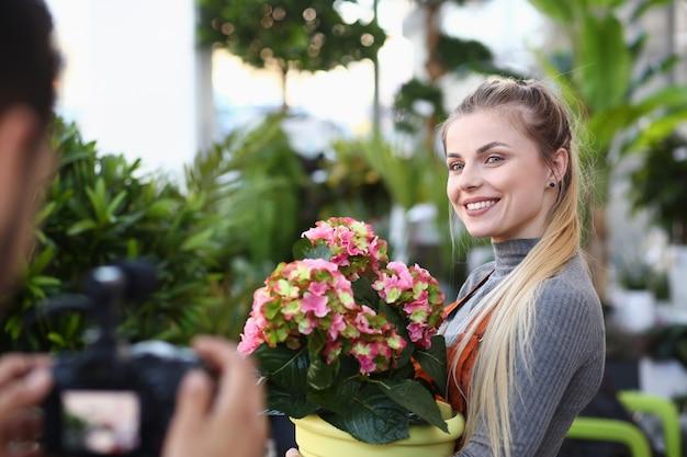 Glücklicher vlogger, der mit blume zum kameramann aufwirft
