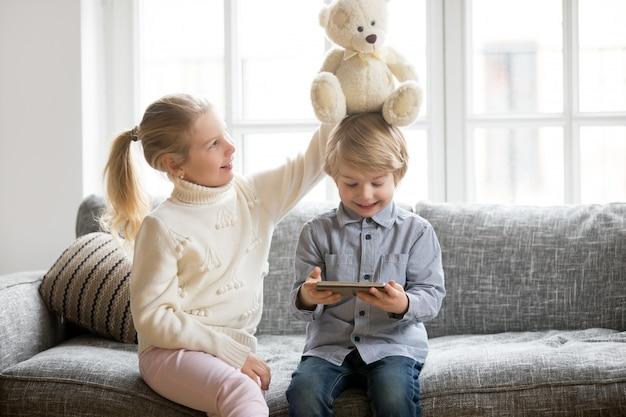 Glücklicher vorschuljunge, der tablette während schwester spielt mit spielzeug verwendet