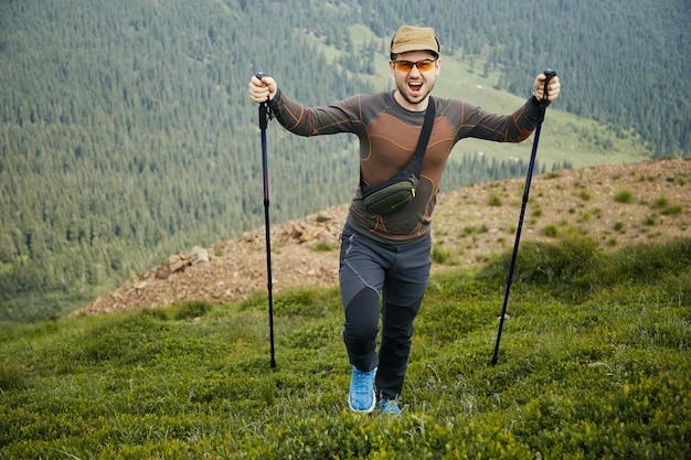 Glücklicher wanderer mit professioneller ausrüstung in den bergen