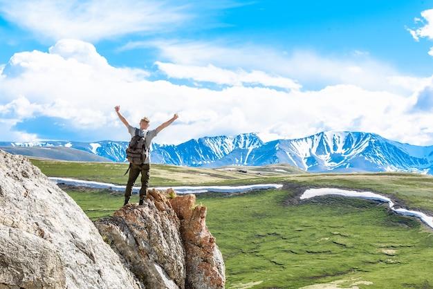 Glücklicher wanderer mit rucksack auf dem gipfel des berges blickt auf die berge