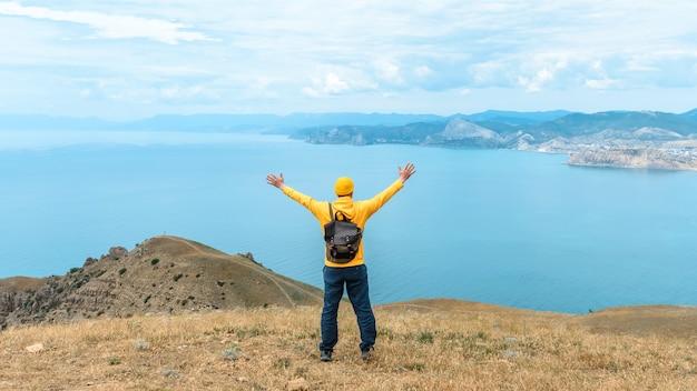 Glücklicher wanderer mit rucksack mit erhobenen händen und blick auf den schönen blick auf das meer. reise- und freizeitkonzept