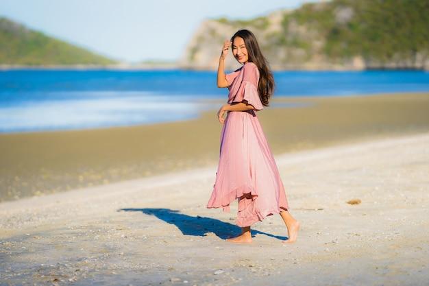 Glücklicher weg des schönen jungen asiatischen frauenlächelns des porträts auf dem tropischen naturstrandmeer im freien