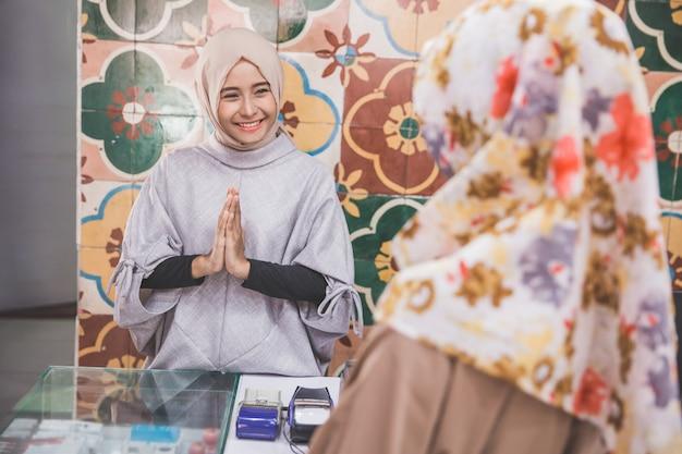 Glücklicher weiblicher arbeiter, der kunden begrüßt
