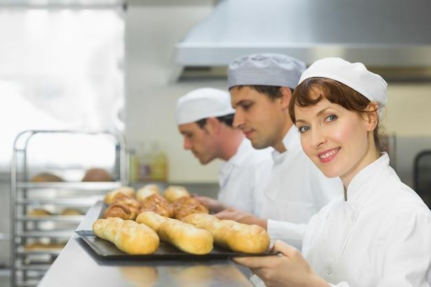Glücklicher weiblicher bäcker, der an der kamera lächelt