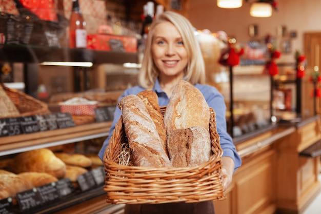 Glücklicher weiblicher bäcker, der an ihrem backhaus arbeitet und brot in einem korb heraushält