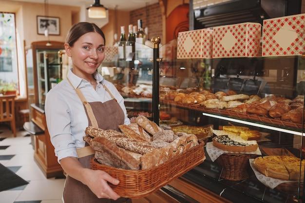 Glücklicher weiblicher bäcker, der zur kamera trägt, die brotkorb trägt und an ihrem bäckereiladen arbeitet