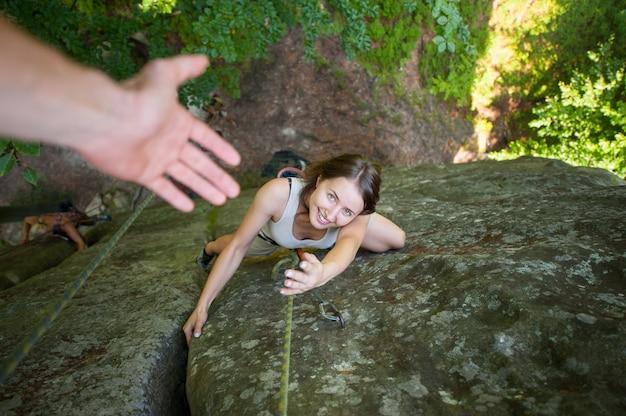Glücklicher weiblicher bergsteiger klettert auf hohem flussstein und versucht, helfende hand zu fangen. ansicht von oben