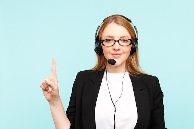 Glücklicher weiblicher call-center-betreiber im blauen studio, der etwas zeigt.