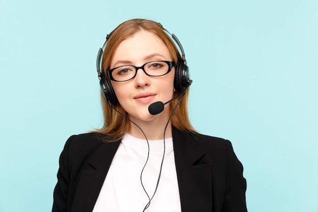 Glücklicher weiblicher callcenter-betreiber im blauen studio.
