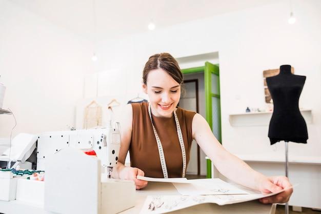 Glücklicher weiblicher designer, der modeskizze betrachtet