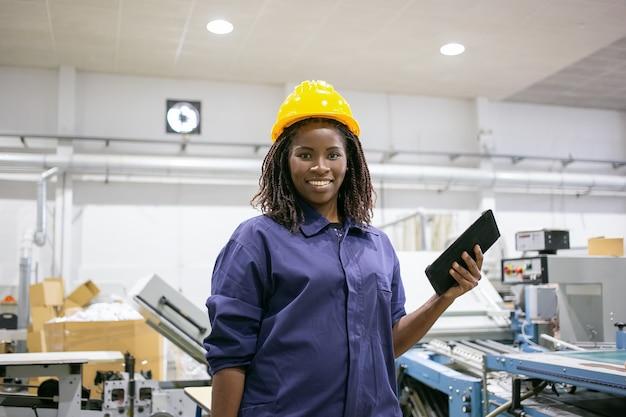 Glücklicher weiblicher fabrikarbeiter im helm und insgesamt, an maschine stehend, tablette haltend, vorne betrachtend und lächelnd