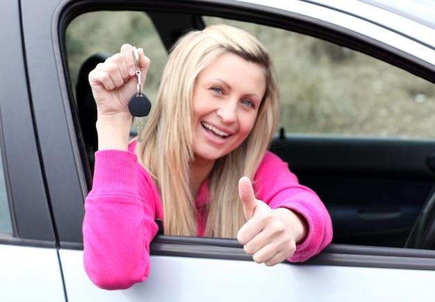 Glücklicher weiblicher fahrer, der einen schlüssel zeigt, nachdem er ein neues auto bying gemacht hat