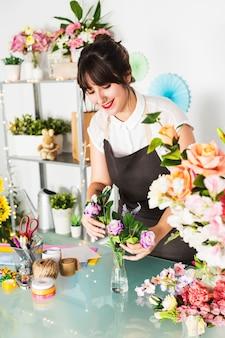 Glücklicher weiblicher florist, der blumen im vase sortiert