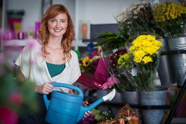 Glücklicher weiblicher florist, der blumen wässert