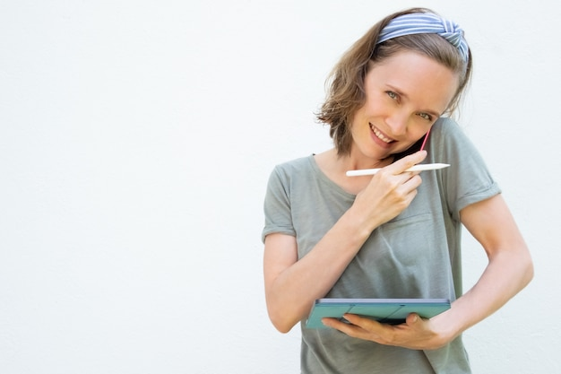 Glücklicher weiblicher freiberufler, der mit tablette und stift arbeitet