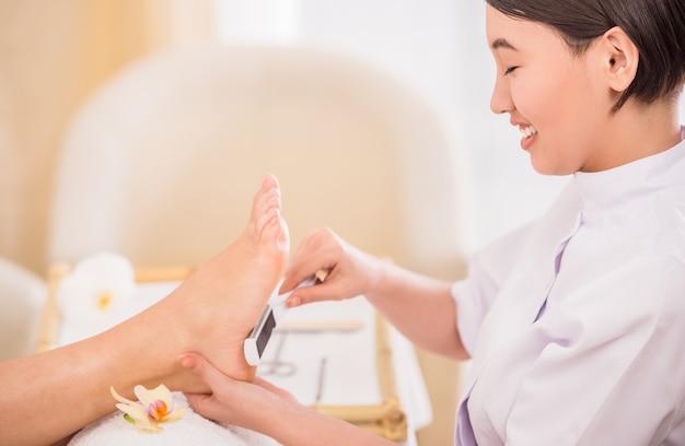 Glücklicher weiblicher fußpfleger, der an einem kunden am badekurort arbeitet.