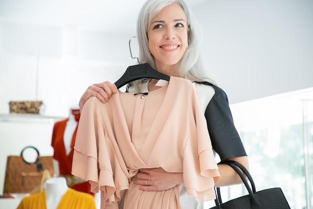 Glücklicher weiblicher käufer, der kleid mit kleiderbügel anwendet und im spiegel schaut. frau, die kleidung im modegeschäft wählt. einkaufs- oder einzelhandelskonzept