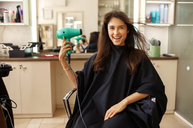 Glücklicher weiblicher kunde, der haartrockner im friseursalon verwendet. frau, die im stuhl im friseursalon sitzt. schönheits- und modegeschäft, professioneller service