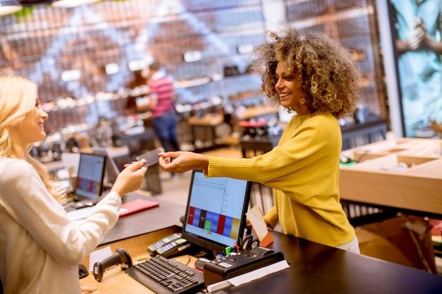 Glücklicher weiblicher kunde, der mit kreditkarte im modeschauzimmer zahlt