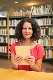 Glücklicher weiblicher kunde mit dem gerät, das öffentlich bibliothek aufwirft