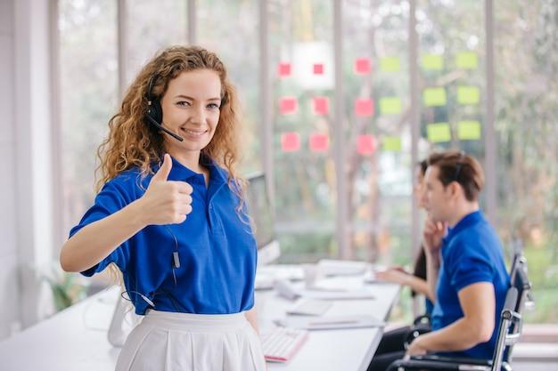 Glücklicher weiblicher kundendienstmitarbeiter, der daumen oben im callcenter zeigt