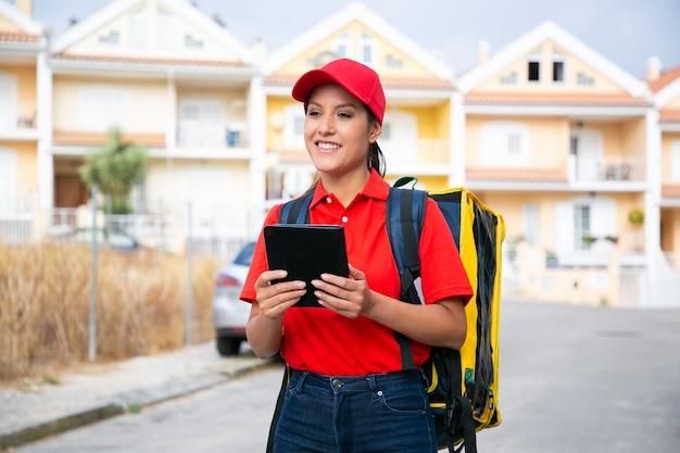 Glücklicher weiblicher kurier, der bestellung liefert und im postdienst arbeitet. lächelnde lieferfrau in der roten kappe und im hemd, die gelben rucksack tragen und tablette halten. lieferservice und online-shopping-konzept