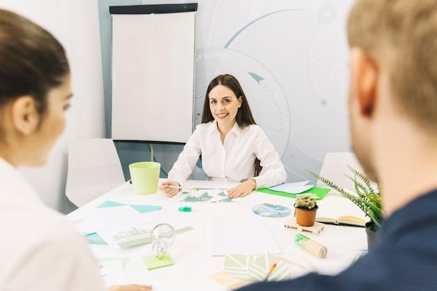 Glücklicher weiblicher manager, der im büro sitzt
