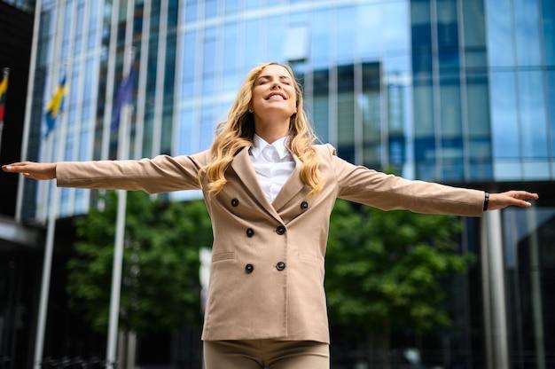 Glücklicher weiblicher manager mit offenen armen im zeichen der freiheit und des erfolgs