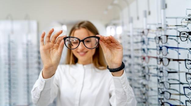 Glücklicher weiblicher optiker mit satz gläsern