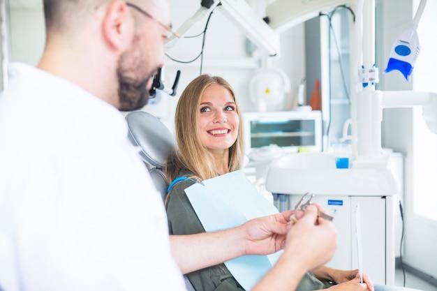 Glücklicher weiblicher patient, der den zahnarzt messendes plastikzahnmodell mit noniustasterzirkel betrachtet