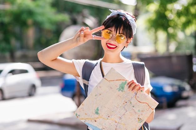 Glücklicher weiblicher reisender mit dem charmanten lächeln, das mit friedenszeichen aufstellt, das vor bunten autos steht