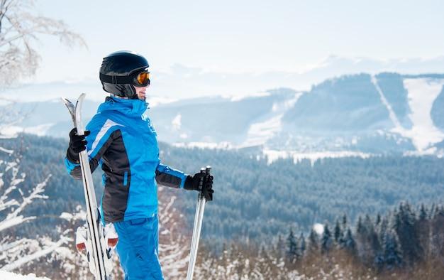 Glücklicher weiblicher skifahrer, der atemberaubende landschaft im wintergebirgs-skigebiet genießt, wegschaut, ski hält