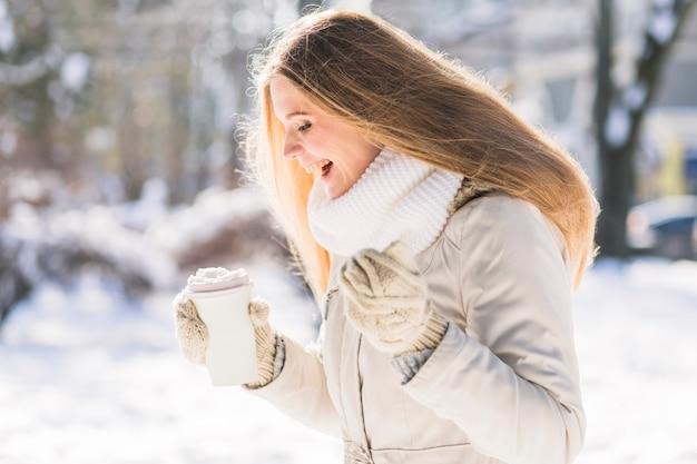 Glücklicher weiblicher tierarzt, der mitnehmerkaffeetasse hält, die im schnee steht