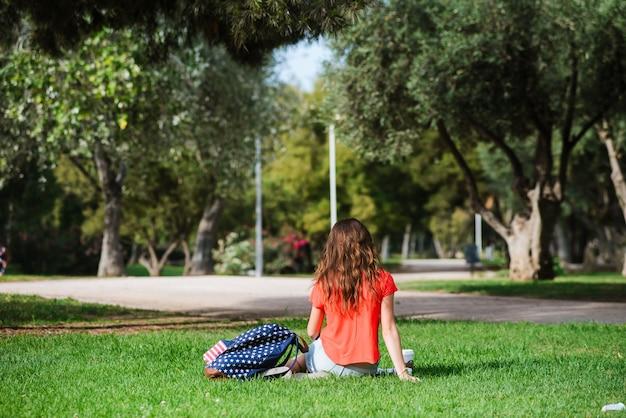 Glücklicher weiblicher tourist, der im park sich entspannt