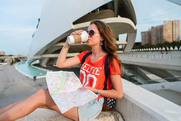 Glücklicher weiblicher tourist mit einer karte in der stadt von künsten und von wissenschaften in valencia
