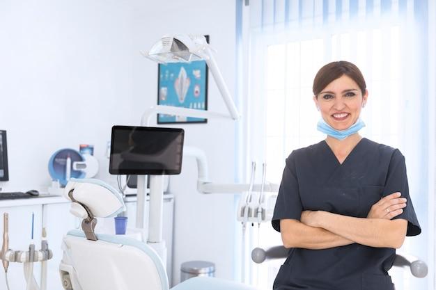 Glücklicher weiblicher zahnarzt in der klinik