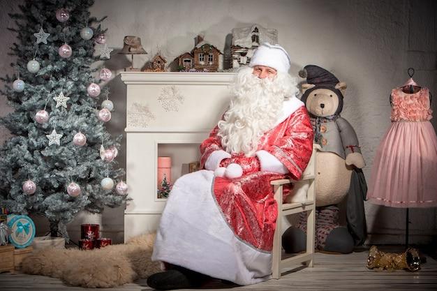Glücklicher weihnachtsmann, der auf der weihnachtsdekoration sitzt