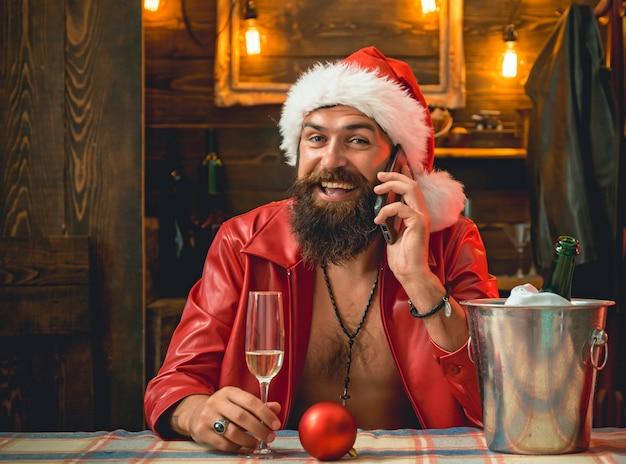 Glücklicher weihnachtsmann, der mit telefon aufwirft