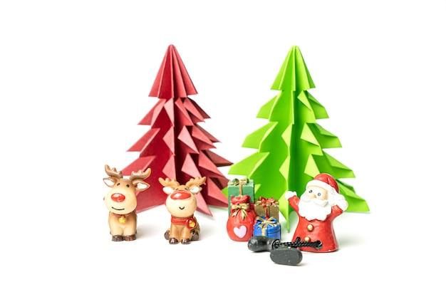 Glücklicher weihnachtsmann, der vor rotem und grünem origami-weihnachtsbaum sitzt