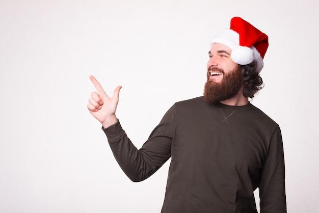 Glücklicher weihnachtsmann, der weihnachtsmütze trägt, zeigt über weißem hintergrund