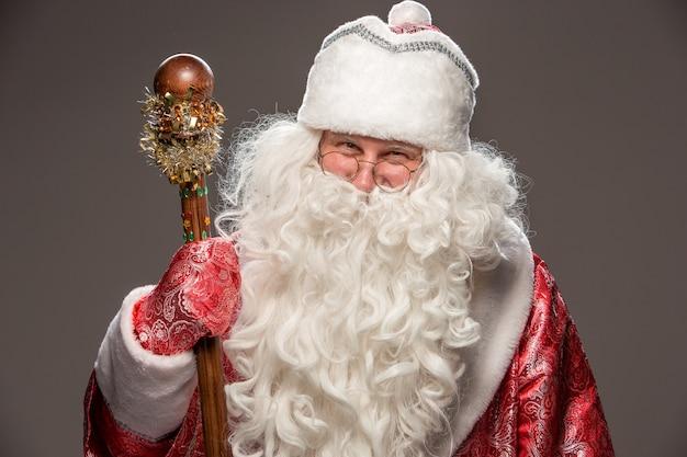 Glücklicher weihnachtsmann in brille mit personal, das kamera auf schwarz betrachtet