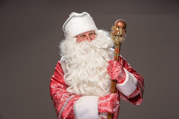 Glücklicher weihnachtsmann in brillen mit personal, das kamera auf schwarzem hintergrund betrachtet