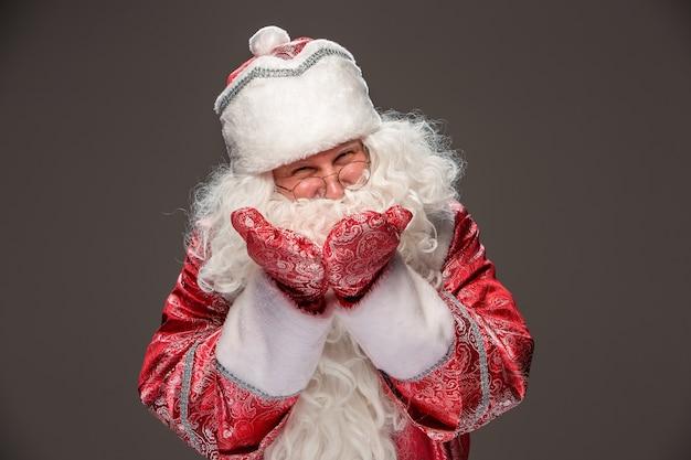 Glücklicher weihnachtsmann in den brillen, die kamera auf dunklem hintergrund betrachten