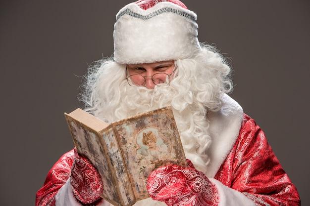 Glücklicher weihnachtsmann in der brille, die altes buch auf schwarz liest